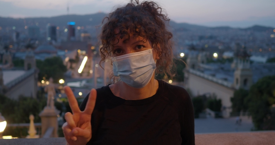 Woman with curly hair and mask on face makes the victory symbol with her fingers during a night in the city. Coronavirus security measures | Shutterstock HD Video #1053106520
