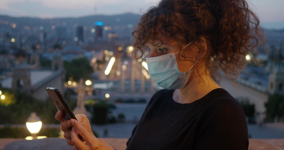 Woman curly hair and mask on face chatting with smartphone one night in the city. Coronavirus security measures | Shutterstock HD Video #1053107312
