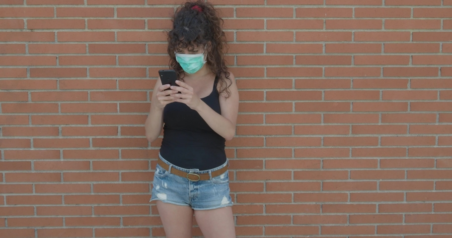 Woman with curly hair and mask on face chatting with smart phone on the street. Coronavirus security measures | Shutterstock HD Video #1053107765