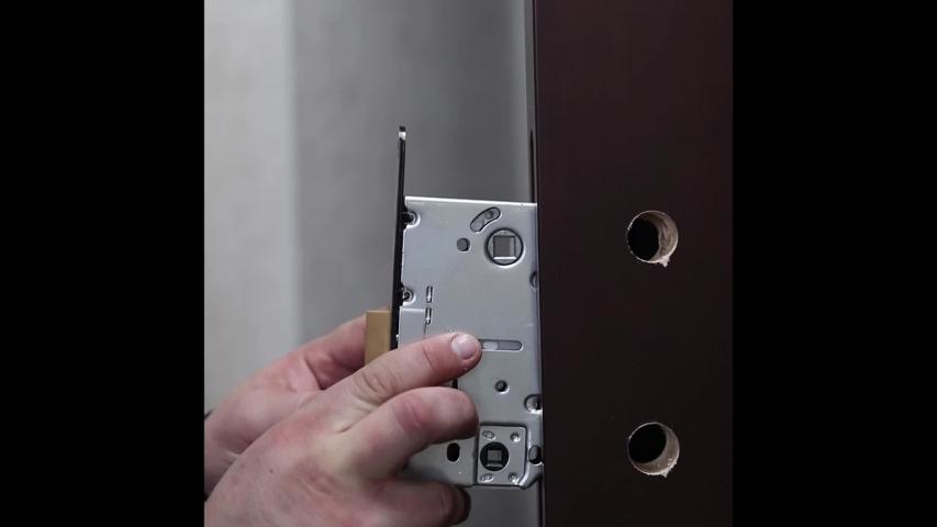 Lock repair close up. The master installs a lock in the door