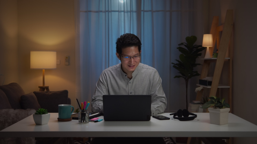 Portrait of asian man and successful middle aged relax cacual cloth working at home, using Laptop Computer and feeling happy. Working from Home at night, self isolation in new normal concept. | Shutterstock HD Video #1053111527
