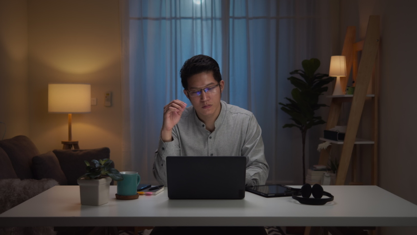 Portrait of asian man and serious millennial hard working at home,thinking and feeling thoughtful.Working from Home overload at night, self isolation in new normal concept.Working late and Overtime | Shutterstock HD Video #1053111824