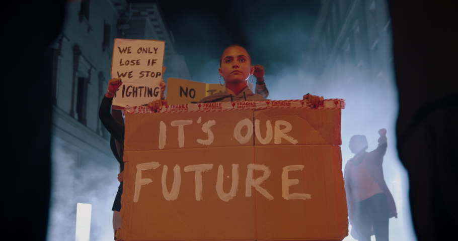 Group of protestors with banners defending their rights in front of the police force. Activists demonstrating against police at night.  Royalty-Free Stock Footage #1053117518