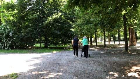Europe, Italy , Milan Sempione park may 2020 - end of the lockdown in Lombardy,elderly lady and foreign caregiver walking in a city park with a walker to help walking disability