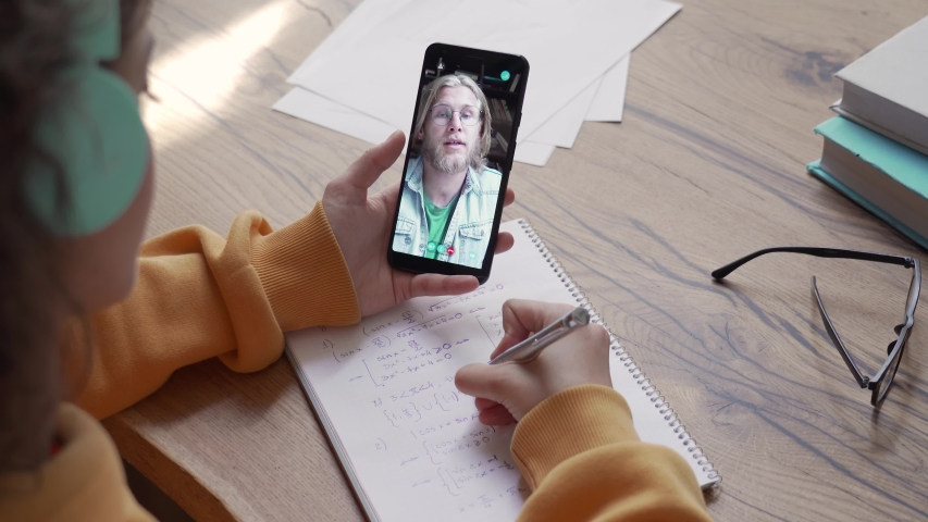 Teen girl school college student wear headphones hold phone distance learn online class with math teacher tutor using mobile zoom app video conference call app write notes. Over shoulder closeup view. Royalty-Free Stock Footage #1053123161