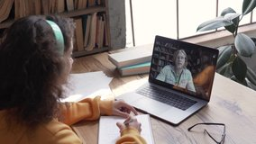 Hispanic teen girl school college student study distance learning talk with online teacher on laptop screen write notes. Elearning zoom video call, videoconference class with tutor. Over shoulder view