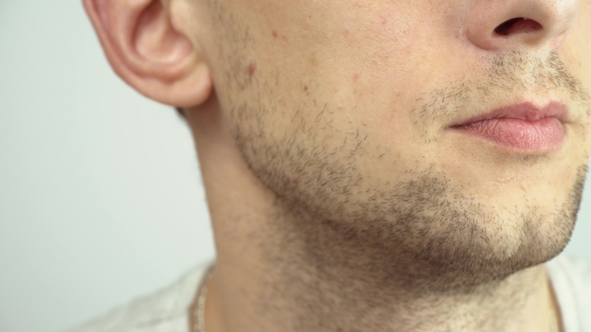 Young man shaving with an electric razor. The guy shaves his beard with a razor close-up macro. | Shutterstock HD Video #1053123728