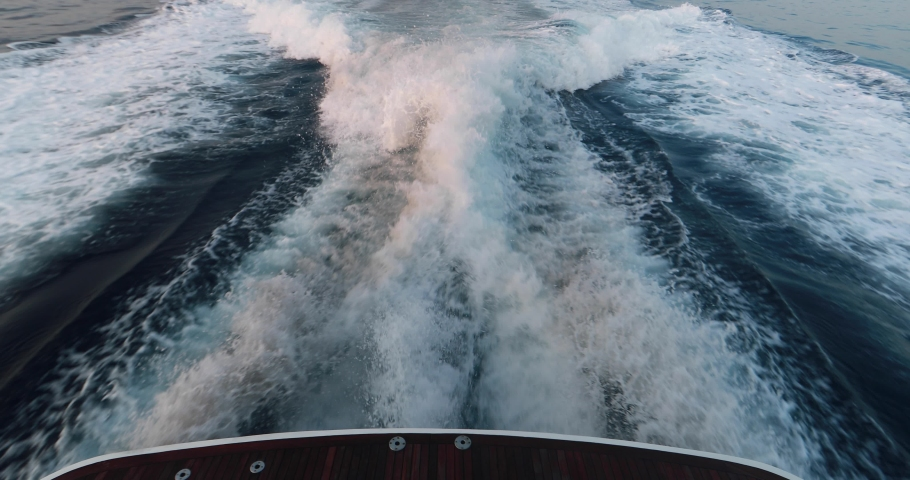Slow motion of the foamy path from the yacht, the boat goes by sea, raging stream of sea water from under the ship at sunset, high speed, luxury life, a clear sunny weather, the Ligurian Sea, nobody | Shutterstock HD Video #1053136199