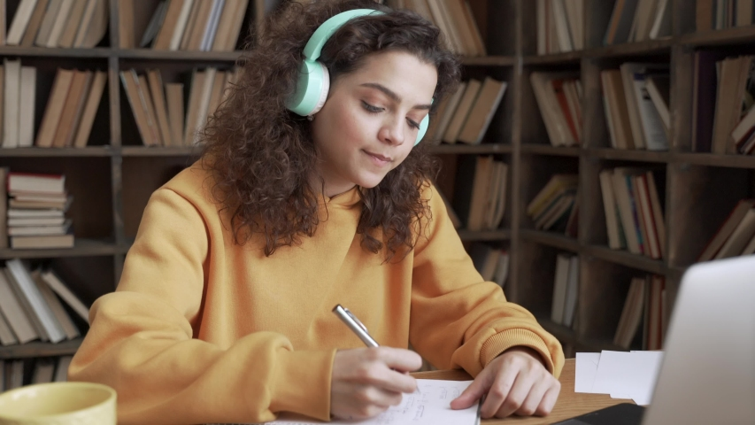 Hispanic teen girl, latin young woman school college student wear headphones learn watching online webinar webcast class looking at laptop elearning making notes or video calling remote teacher. Royalty-Free Stock Footage #1053139646