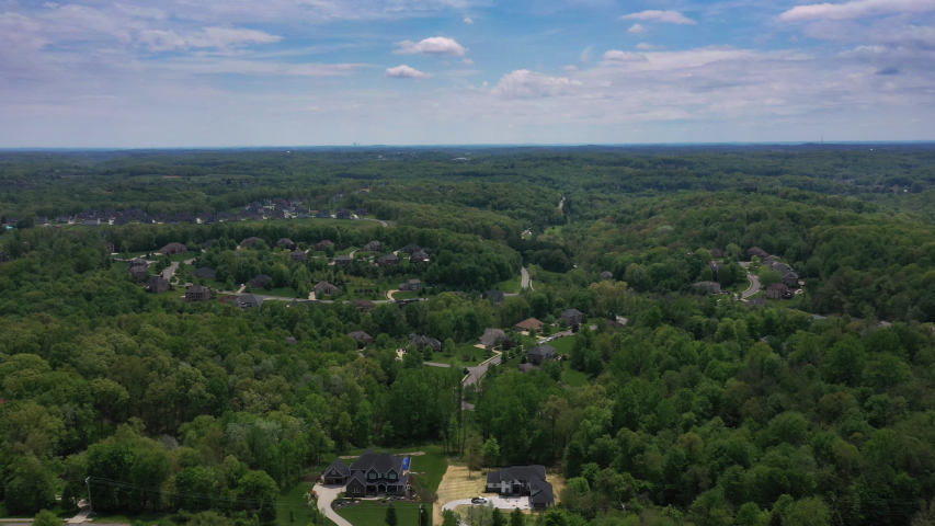 A wide aerial establishing shot of a typical Western Pennsylvanian residential neighborhood. Upscale homes below. The Pittsburgh skyline seen in the far distance.   | Shutterstock HD Video #1053146933