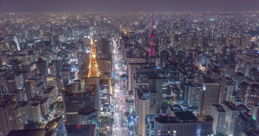 Aerial hyperlapse of huge city at night with buildings, antenas and cars driving.Wide shot of Paulista avenue and Sao Paulo. Brazil