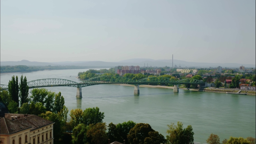 Timelapse of Danube and Mária Valéria bridge. Traffic in the bridge. Slight smog and factory chimney in the distance. Group of block houses. | Shutterstock HD Video #1053148100