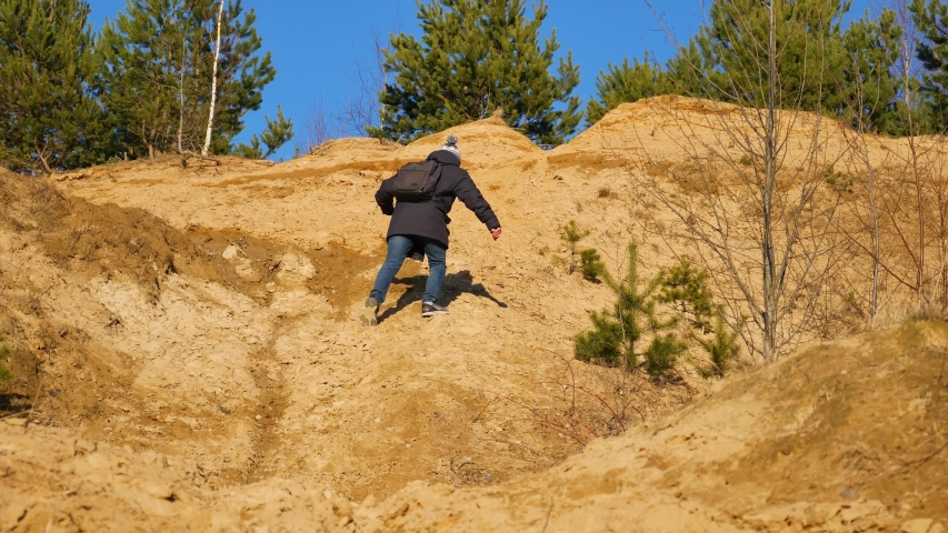 A man with a backpack climbs the mountain. The tourist goes to the top, all in the sand. Sand mountain and trees on top. | Shutterstock HD Video #1053150497