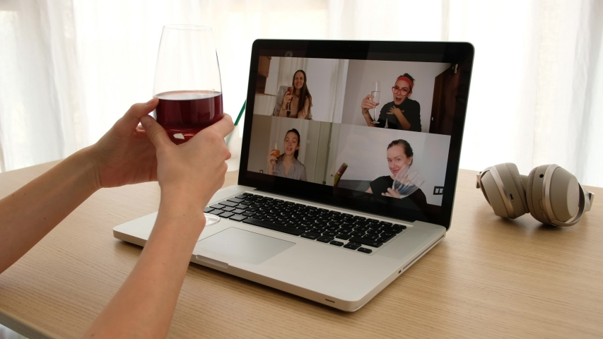 Crop female sitting with glass of wine at table and making video call via laptop with girlfriends while having remote party during coronavirus outbreak | Shutterstock HD Video #1053151766