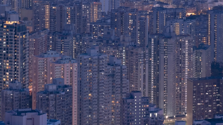 Crowded city with lights turning on and off at night. Hong Kong city apartment buildings at night.  Royalty-Free Stock Footage #1053152009