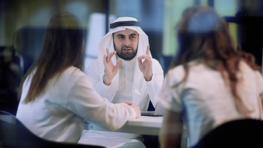 Arab businessman in a meeting with business partners leads a conversation. | Shutterstock HD Video #1053152396