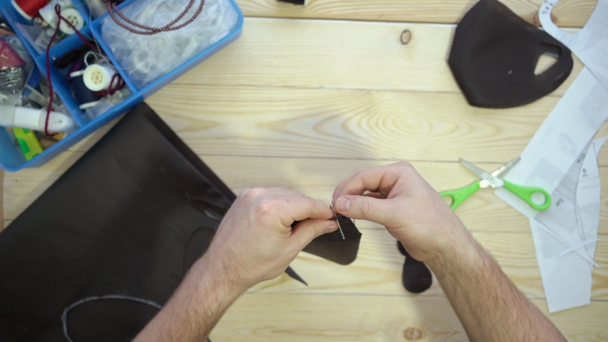 Mens hands sew with a needle. fabrics and sewing accessories for sewing an anti-virus mask. Zero waste and quarantine concept. Homemade black facemask against virus infection. | Shutterstock HD Video #1053160058
