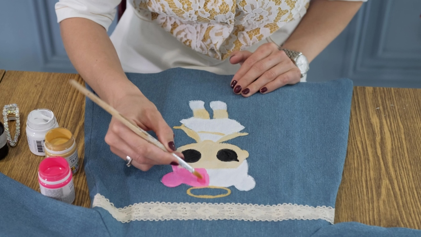 Designer painting on denim cloth. Making personal collection dresses for girls | Shutterstock HD Video #1053160592