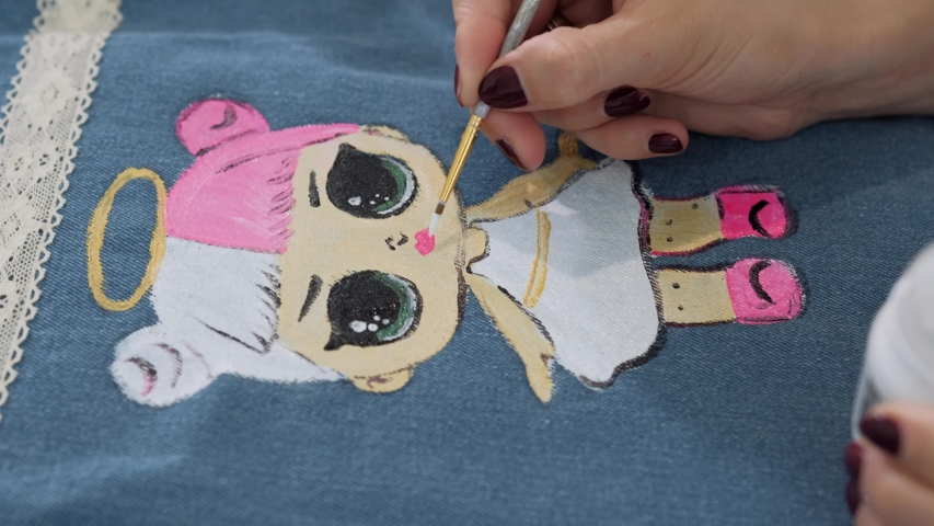 Designer painting on denim cloth. Making personal collection dresses for girls | Shutterstock HD Video #1053160595