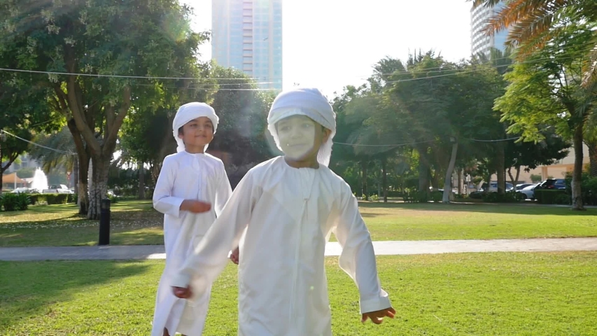Kids playing outdoor on the meadow. Children wearing traditional united arab emirates kandura having fun