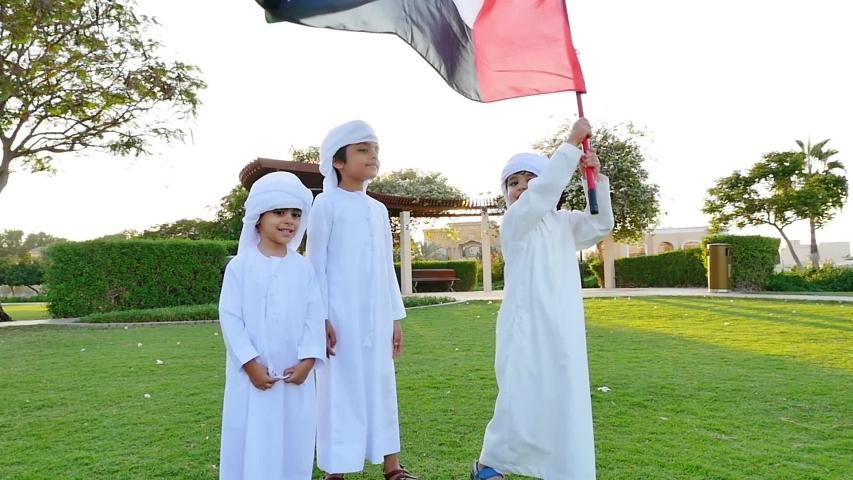 Kids playing outdoor on the meadow. Children wearing traditional united arab emirates kandura having fun