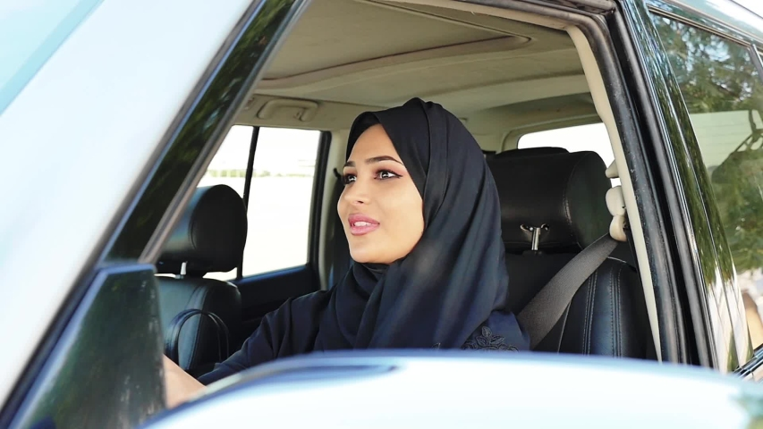 Beautiful woman wearing traditional clothes from united arab emirates. Young lady driving her car in Dubai