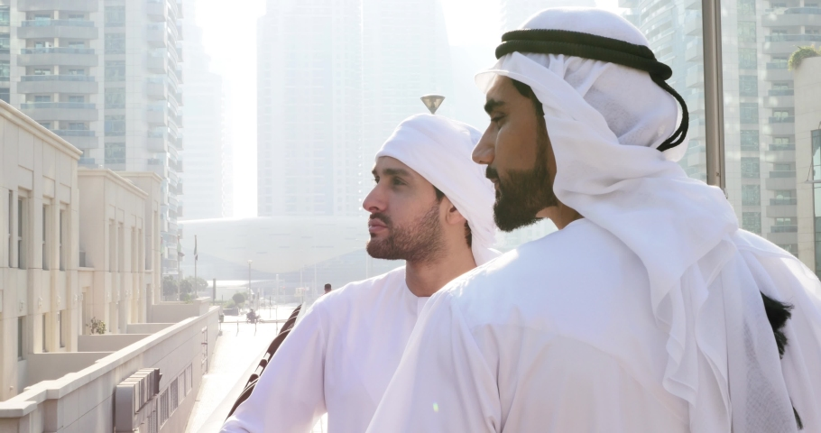 Two young businessmen going out in Dubai. Friends wearing the kandura traditional male outfit walking in Marina | Shutterstock HD Video #1053162698