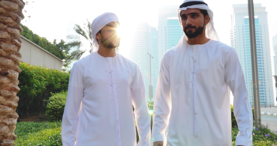 Two young businessmen going out in Dubai. Friends wearing the kandura traditional male outfit walking in Marina | Shutterstock HD Video #1053162713