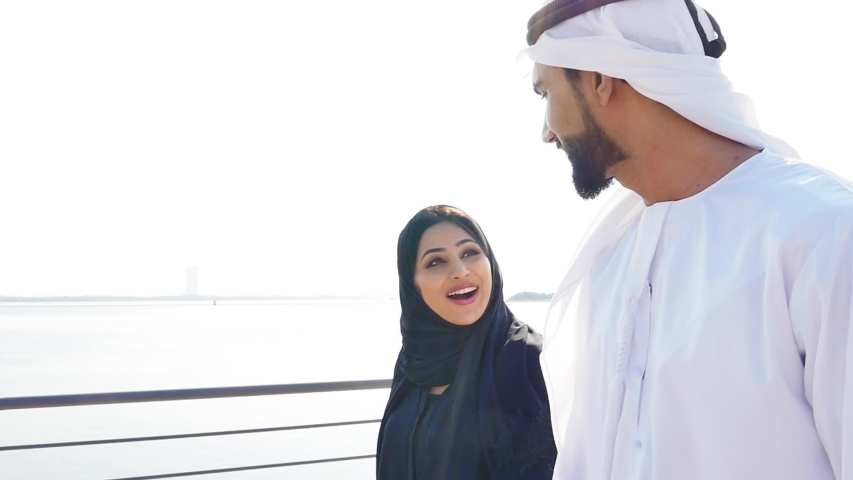 Couple spending time together in Dubai. Man and woman wearing kanura and hijab walking near the ocean and watching the skyline