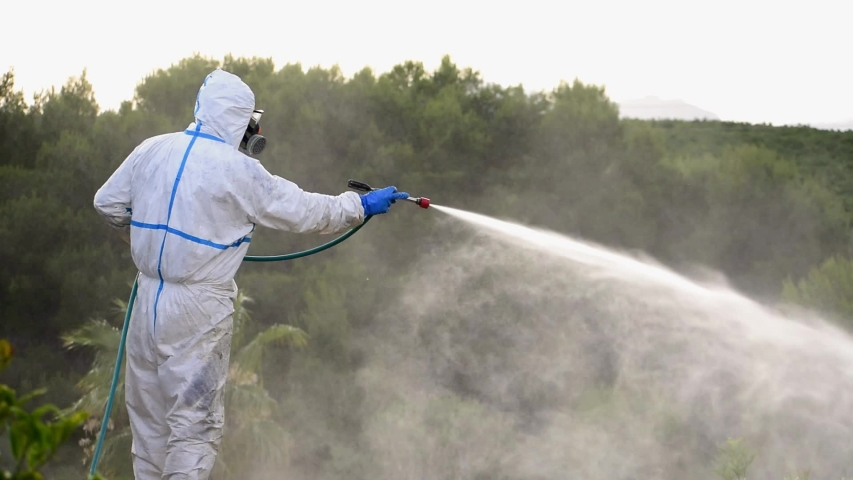 Spray ecological pesticide. Farmer fumigate in protective suit and mask lemon trees. Man spraying toxic pesticides, pesticide, insecticides  Royalty-Free Stock Footage #1053166886