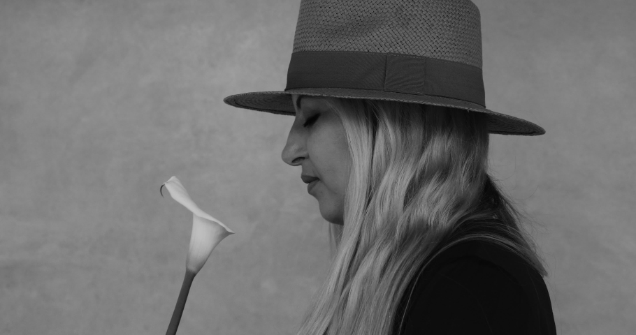 Side-profile of an elegant woman with hat, smelling on a white calla lily flower, then turning to the camera smiling. Real-time footage in black and white.