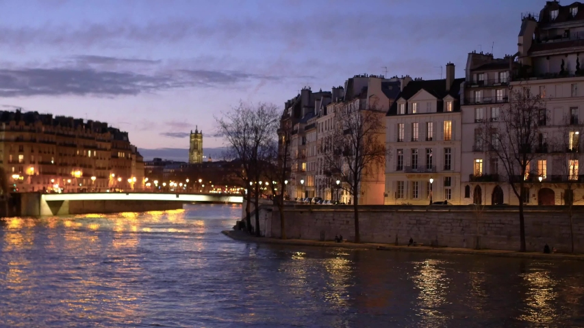 "Cityscape of Paris, France. View on the Seine river and on the ""île de la cité"" and the ""île saint louis"". Filmed at night just after the sunset."