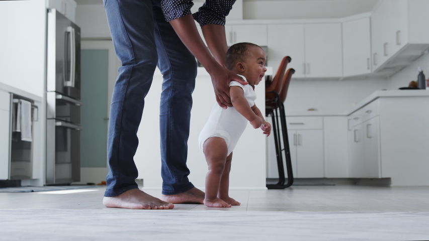 Close up of father encouraging smiling baby son to take first steps and walk at home - shot in slow motion | Shutterstock HD Video #1053167300