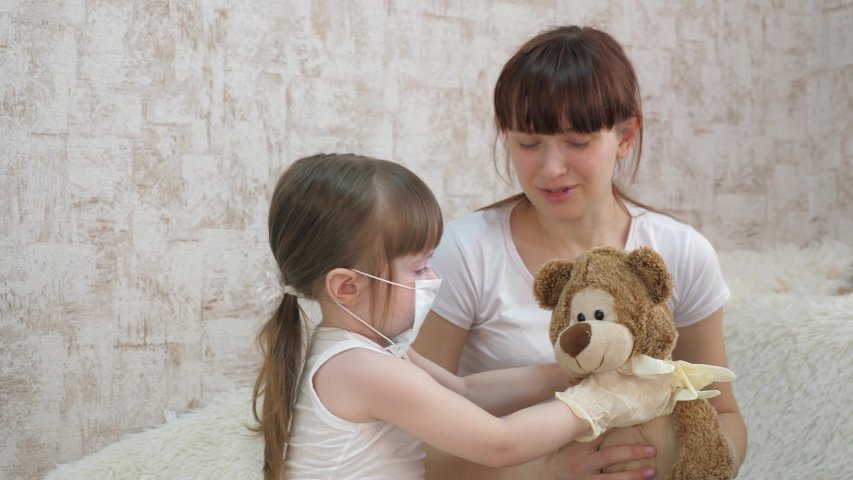 Child put on a protective medical mask and rubber gloves on handles. children play by doctors with toy bear. child plays in hospital. game by doctor, nurse, veterinarian, treats patient with vaccine.
