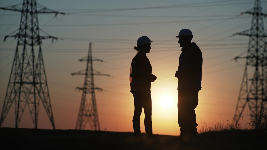 Woman and man electric industry experts in protective helmets discussing the construction of a power line to supply electricity to city at sunset, silhouette