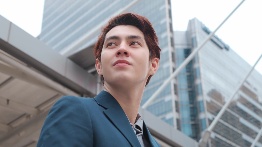 360 Degree Tracking Shot of the Thoughtful Businessman mixed wearing a Suit looking out while standing near modern Office Building. 4K Slow Motion Corporate Shot with Moving Around 360 Camera. | Shutterstock HD Video #1053175355