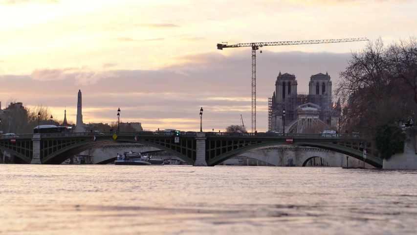 View on the Seine river in Paris, France. Filmed in the sunset. In the background, there is the famous Notre-dame cathedral (after the fire of 2019) and a big crane.   Shutterstock HD Video #1053180080
