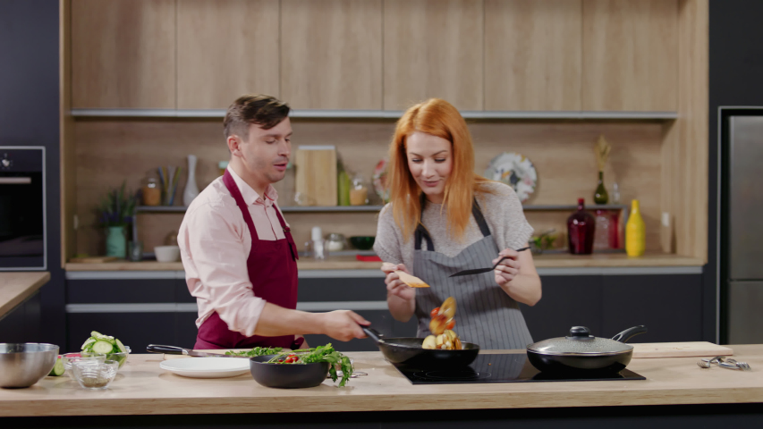 Cooking show hosts chefs, male and female, cooking in the kitchen studio set. Morning TV cooking programme. Shot on ARRI Alexa Mini Royalty-Free Stock Footage #1053180893