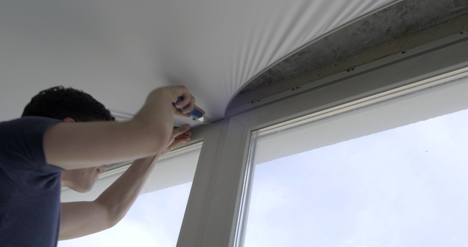 Man tucks edges of fabric ceiling into fixtures around room's perimeter, near window, most difficult part, accurate work, stretch ceilings, lot of fabric tension, stretches material, unbearable heat | Shutterstock HD Video #1053181484