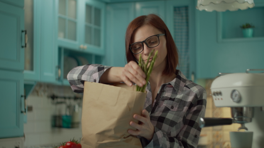 Young adult woman in glasses holding paper bag with fresh food and laying out vegetables and eggs standing on blue kitchen at home. Female puts on table asparagus and other food. Close up