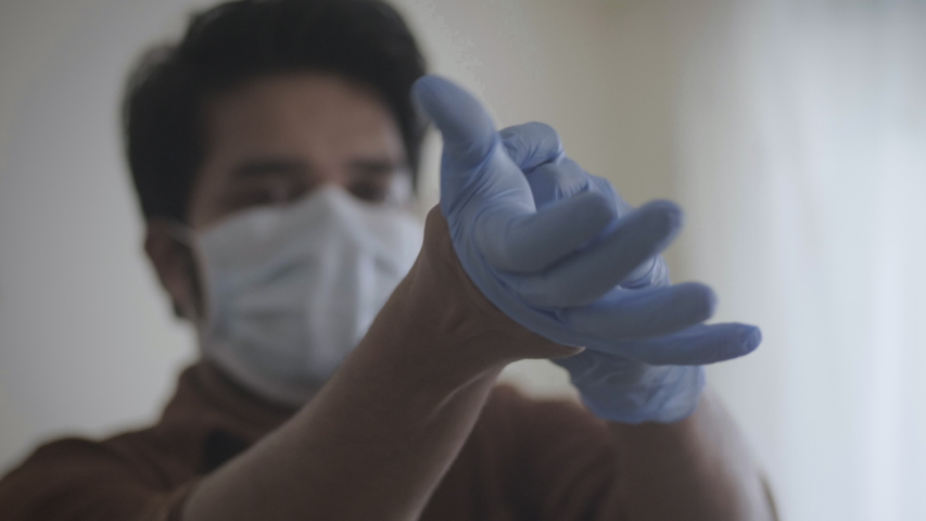 A close up shot of a male essential health worker following safety measures by wearing hand gloves amid coronavirus or COVID 19 epidemic or Pandemic Royalty-Free Stock Footage #1053182987