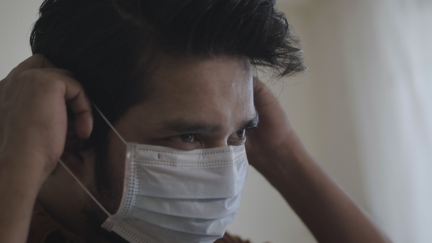 A close up shot of a young man or male wearing or putting protective face mask amid Coronavirus or COVID 19 epidemic or pandemic