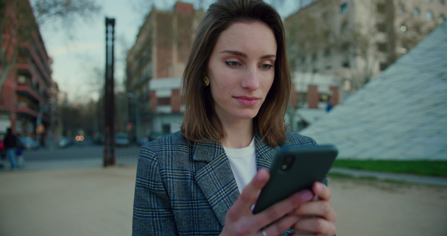 Slow Motion Arc Shot of Young Woman Typing on Smartphone on the Street. Attractive Girl Wearing Grey Plaid Blazer and Using Application on Mobile Device for Messaging. Communication Technology Concept | Shutterstock HD Video #1053186611