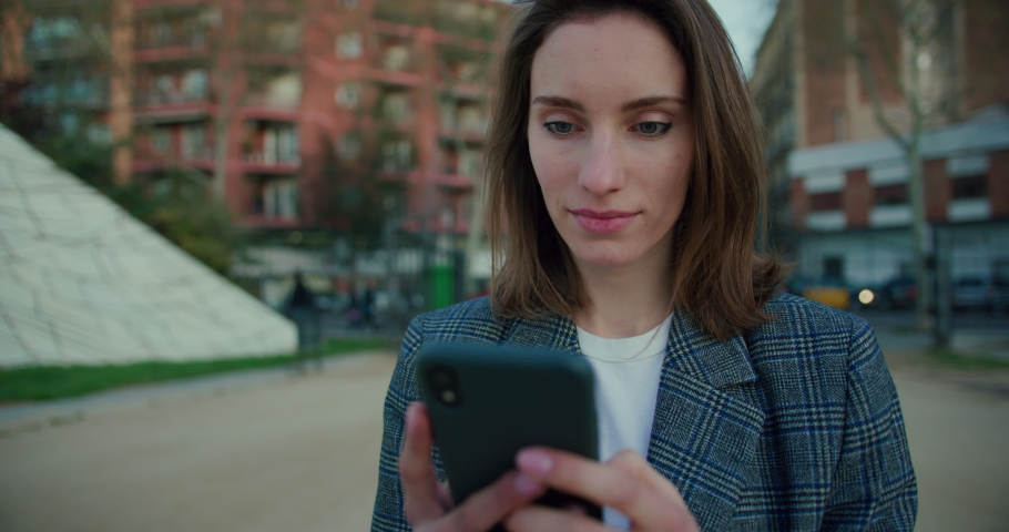 Slow Motion Arc Shot of Young Woman Typing on Smartphone on the Street. Attractive Girl Wearing Grey Plaid Blazer and Using Application on Mobile Device for Messaging. Communication Technology Concept   Shutterstock HD Video #1053186611