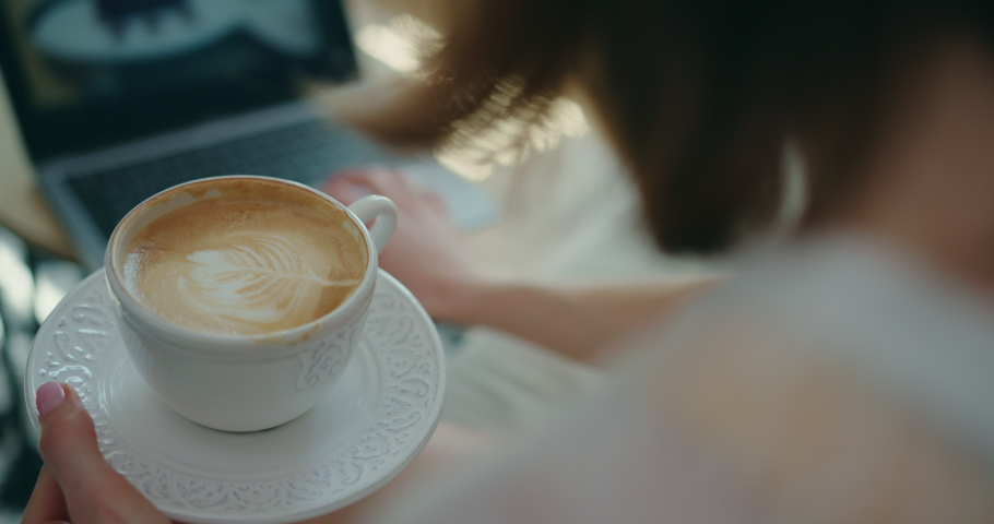 Close-Up of Young Woman's Hands Elegantly Holding Cup of Coffee with Milk and Saucer. Over-the-Shoulder Slow Motion Shot of Girl Sitting in front of Laptop at Home, Watching Video, Drinking Cappuccino | Shutterstock HD Video #1053186617