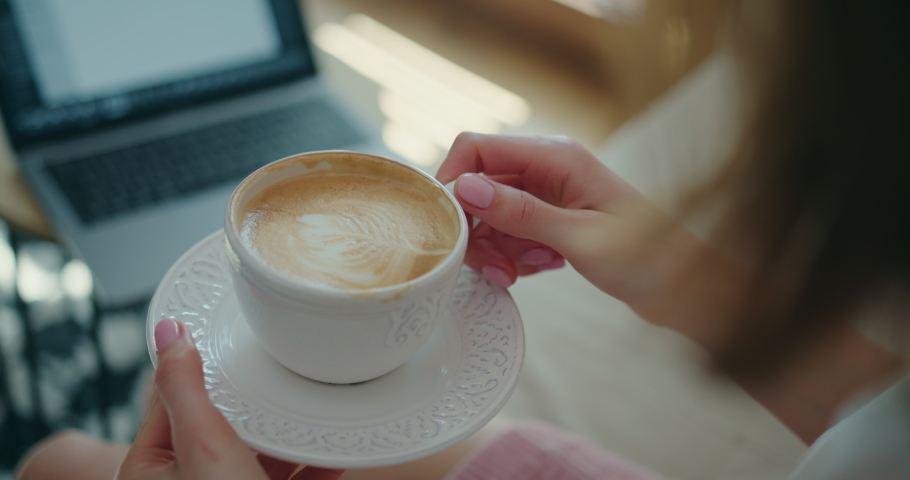 Close-Up of Young Woman's Hands Elegantly Holding Cup of Coffee with Milk and Saucer. Over-the-Shoulder Slow Motion Shot of Girl Sitting in front of Laptop at Home, Watching Video, Drinking Cappuccino   Shutterstock HD Video #1053186617