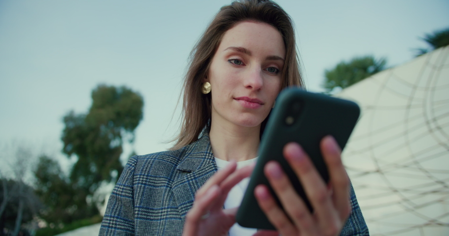 Low Angle Arc Shot of Young Woman Typing on Smartphone While Out in Park. Attractive Girl Wearing Grey Plaid Blazer and Using Application on Mobile Device for Online Communication. Slow Motion   Shutterstock HD Video #1053186620