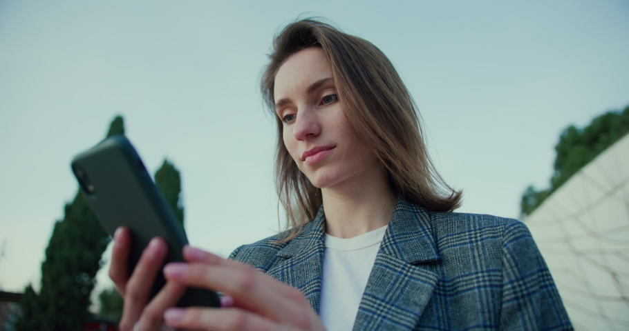 Low Angle Arc Shot of Young Woman Typing on Smartphone While Out in Park. Attractive Girl Wearing Grey Plaid Blazer and Using Application on Mobile Device for Online Communication. Slow Motion | Shutterstock HD Video #1053186620