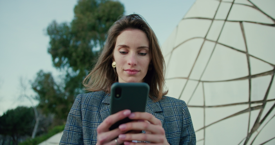 Young Woman Typing on Smartphone While Taking Walk in Park. Low Angle Portrait of Attractive Girl Wearing Grey Plaid Blazer and Using Mobile Device to Text Messages. Slow Motion Backward Tracking Shot | Shutterstock HD Video #1053186623