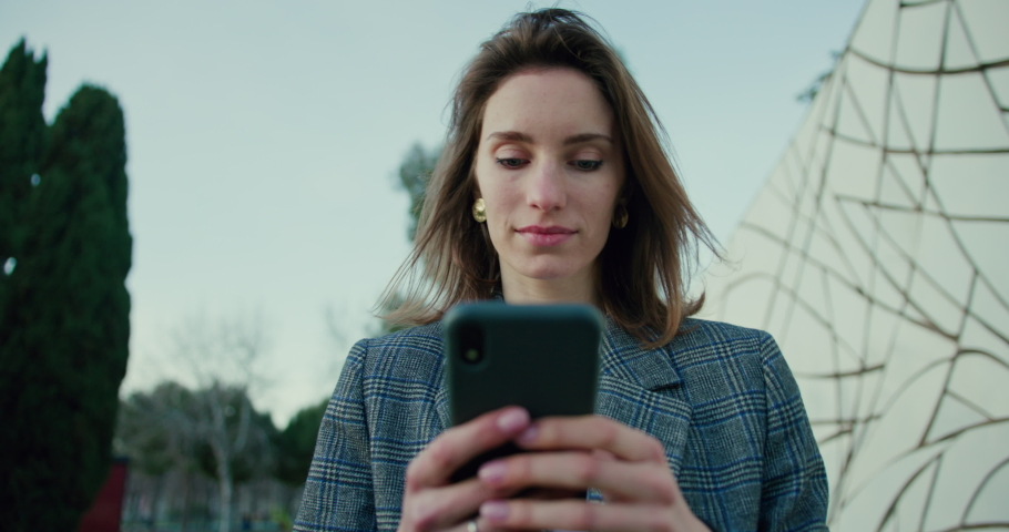 Young Woman Typing on Smartphone While Taking Walk in Park. Low Angle Portrait of Attractive Girl Wearing Grey Plaid Blazer and Using Mobile Device to Text Messages. Slow Motion Backward Tracking Shot   Shutterstock HD Video #1053186623